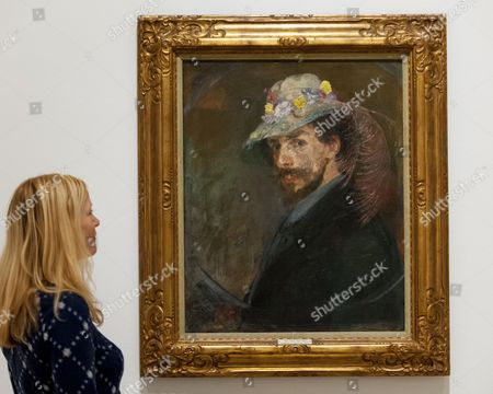 "A staff member views ""Self-portrait with flowered hat, 1893"" at the preview of Intrigue: James Ensor by Luc Tuymans"