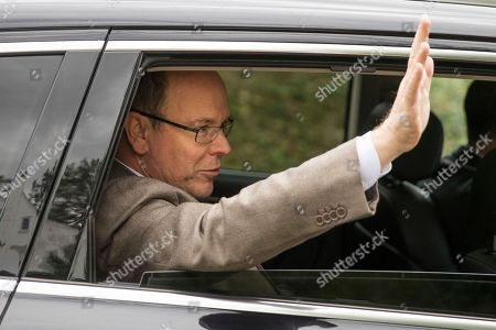 Prince Albert II of Monaco waves after touring a house he recently purchased in Philadelphia, . It's the home where his mother, Oscar-winning actress Grace Kelly, grew up and accepted a marriage proposal from Prince Rainier III of Monaco