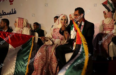 A Palestinian bride and her wounded groom who was wounded in the summer 2014 Israel-Hamas war, wave Palestinian and Emirate flags during a mass wedding celebration ceremony, in Gaza City, . Nineteen Palestinian wounded grooms took part in the mass wedding aided by Sheikh Nahyan bin Mubarak Al Nahyan, United Arab Emirates Minister of Culture, Youth and Community Development
