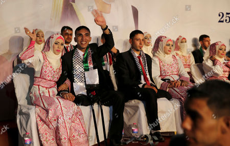 A Palestinian bride and her wounded groom who were wounded in the summer 2014 Israel-Hamas war, great their relatives while they attend a mass wedding celebration ceremony, in Gaza City, . Nineteen Palestinian wounded grooms are taking part in the mass wedding aided by Sheikh Nahyan bin Mubarak Al Nahyan, United Arab Emirates Minister of Culture, Youth and Community Development