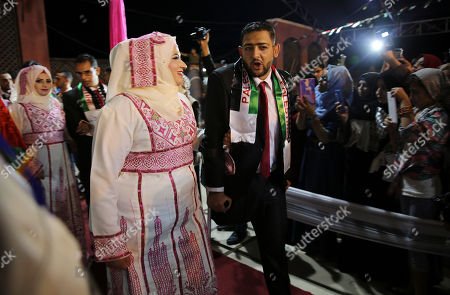 A Palestinian bride walk with her wounded groom who was wounded in the summer 2014 Israel-Hamas war, to attend a mass wedding celebration ceremony, in Gaza City, . Nineteen Palestinian wounded grooms are taking part in the mass wedding aided by Sheikh Nahyan bin Mubarak Al Nahyan, United Arab Emirates Minister of Culture, Youth and Community Development