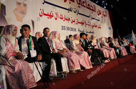 """Palestinian brides and wounded grooms who were wounded in the summer 2014 Israel-Hamas war, sit on stage during a mass wedding celebration ceremony, in Gaza City, . Nineteen Palestinian wounded grooms are taking part in the mass wedding aided by Sheikh Nahyan bin Mubarak Al Nahyan, United Arab Emirates Minister of Culture, Youth and Community Development. Arabic reads that """"the mass wedding of wounded grooms, thanks Sheikh Nahyan bin Mubarak Al Nahyan"""