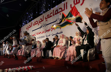 """A Palestinian groom who was wounded in the summer 2014 Israel-Hamas war, wave Palestinian and Emirate flags while a band performs a traditional folklore dance, Dabka, during a mass wedding celebration ceremony in Gaza City, . Nineteen Palestinian wounded grooms took part in the mass wedding aided by Sheikh Nahyan bin Mubarak Al Nahyan, United Arab Emirates Minister of Culture, Youth and Community Development. Arabic reads that """"The mass wedding of wounded grooms, Thanks Sheikh Nahyan bin Mubarak Al Nahyan"""