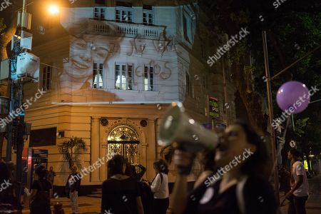 A photo of Lucia Perez,16-year-old girl that was rapped and killed in Argentina, is projected on a building as women participate in a demonstration against gender violence in Rio de Janeiro, Brazil, . Women in Brazil organized protests condemning violence against women following the recent brutal gang rape of a woman on the outskirts of Rio de Janeiro by suspected drug dealers