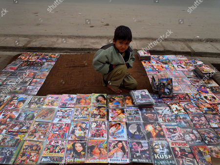 """An Afghani boy, Ahmad Shah, 7, displays bootleg movies for sale along a road side in Jalalabad, Afghanistan, . Fawad Mohammadi, the young Afghan star of """"Buzkashi Boys,"""" the Oscar-nominated movie that didn't win in the live action short film category, was discovered by director Sam French while peddling maps to foreigners in the Afghan capital, one of an untold number of Afghan youths hustling in the streets to help earn money for their families"""