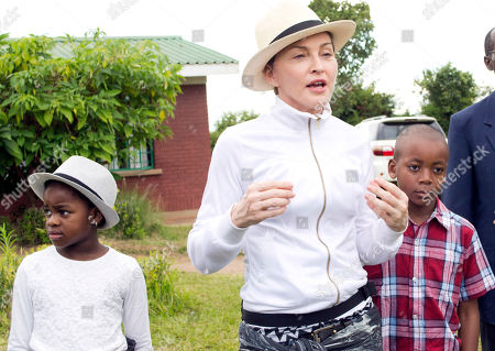 Madonna AP10ThingsToSee - Madonna, center, tours the Mphandura orpahange near Lilongwe, Malawi on . The performer is spending her fourth day in the southern African country from where she adopted two children David Banda, right and Mercy James, left