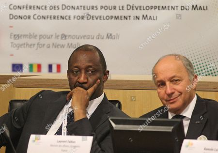 Laurent Fabius, Tieman Coulibaly French Foreign Minister Laurent Fabius, right, and his Mali counterpart Tieman Coulibaly listen during the Donor Conference for Development in Mali, in Brussels, . Mali aims to raise 2 billion euros ($2.6 billion) at an international donor conference to fund its recovery after Islamist militants marched on Bamako this year, prompting a French military intervention