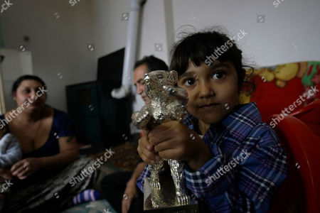 Stock Image of Sandra Mujic, the daughter of the unexpected movie star, Nazif Mujic, plays with her favorite toy - her dad's best actor award, the Silver Bear in the living room o their home in the village of Poljice, 150 kms northeast of Sarajevo, on . People in the Gypsy village of Poljice say they will never forget the night they almost fell off their chairs two months ago. Did they really hear the elegant woman on TV correctly? Could she really be talking about their neighbor, the toothless man who passed his days selling scrap metal and lived in the shack down the road? The camera switched to a frightened-looking Najif Mujic. Yes it was him. THEIR Nazif _ who had just left Matt Damon and Jude Law in the dust to win the best actor award at the Berlin Film Festival