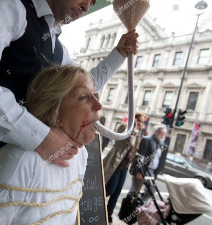 People for the Ethical Treatment of Animals founder Ingrid Newkirk with a funnel of feed in her mouth held by with helper Robbie Le Blanc as they pose during a media event outside an upmarket department store, to campaign against sale of foie gras in the store, and the way it is made in London, Wednesday, March, 20, 2013. Foie gras is made from the liver of specially fattened duck or goose by force feeding