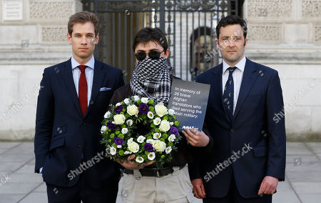 """Former British soldiers Patrick Hennessey, left, and Jake Wood, right, and Interpreter """"Mohammad"""", centre, hold a wreath outside the Foreign Office in London, . Campaigners and two former British soldiers gathered to deliver a box with over 70,000 signatures calling on the UK government to grant Afghan interpreters asylum, a wreath was laid in memory of the 26 Afghan interpreters who have already been killed while serving with British forces"""