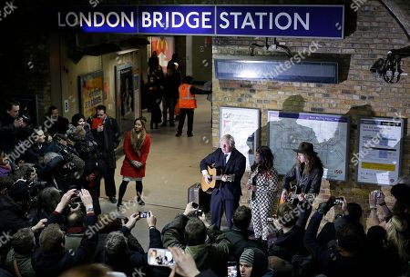 """Boris Johnson, Mayor of London, holds a guitar as he joins pop singer Misha B and Josh Osho during a media event to promote """"Gig 2012' the annual busking competition for buskers on the London Underground train network in London, Tuesday, March, 26, 2013. The competition gives talented young musicians the opportunity to win a converted year long busking license on the underground, singer Misha B used busking to overcome her stage fright, before finding fame on the X Factor TV show"""