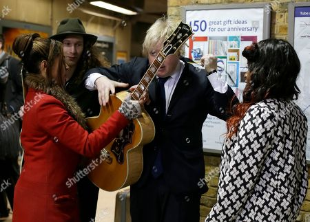 """Boris Johnson, Mayor of London, puts on a guitar as he joins pop singer Misha B, right, and Josh Osho, right wearing hat, during a media event to promote """"Gig 2012' the annual busking competition for buskers on the London Underground train network in London, Tuesday, March, 26, 2013. The competition gives talented young musicians the opportunity to win a converted year long busking license on the underground, singer Misha B used busking to overcome her stage fright, before finding fame on the X Factor TV show"""