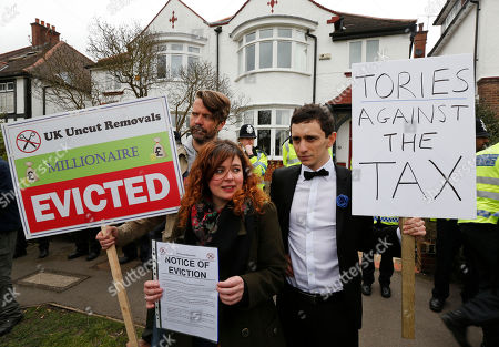 Protesters hold placards and a fake eviction notice for David Freud, Britain's Parliamentary Under Secretary of State for Welfare Reform, during a demonstration outside his house in north London, . Protesters from the Ukuncut Group are campaigning across the UK against the government's planned so-called bedroom tax and its plans for cuts to benefits