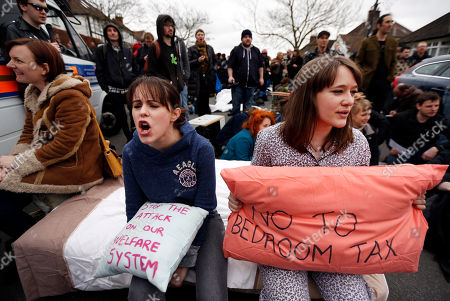 Stock Picture of Protesters holding pillows, chant anti-cuts slogans during a protest outside the house of David Freud, Britain's Parliamentary Under Secretary of State for Welfare Reform, in north London, . Protesters from the Ukuncut Group are campaigning across the UK against the government's planned so-called bedroom tax and its plans for cuts to benefits