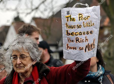 A protester holds a sign outside the house of David Freud, Britain's Parliamentary Under Secretary of State for Welfare Reform, in north London, . Protesters from the Ukuncut Group organized actions across the UK as part of a campaign against the government's planned so-called bedroom tax and cuts to benefits