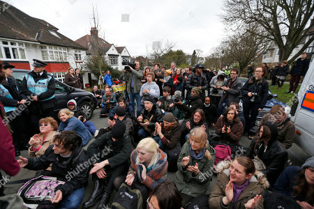 Stock Photo of Protesters chant anti-cuts slogans during a protest outside the house of David Freud, Britain's Parliamentary Under Secretary of State for Welfare Reform, in north London, . Protesters from the Ukuncut Group organized actions across the UK as part of a campaign against the government's planned so-called bedroom tax and cuts to benefits