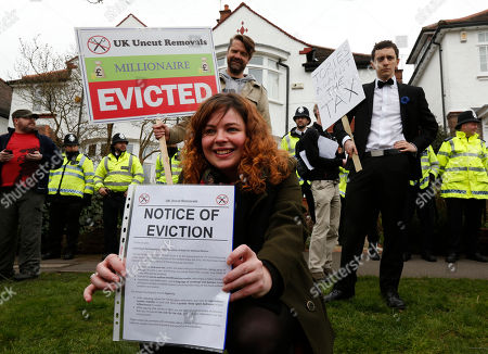 Stock Image of A protester holds a fake eviction notice for David Freud, Britain's Parliamentary Under Secretary of State for Welfare Reform, during a demonstration outside his house in north London, . Protesters from the Ukuncut Group are campaigning across the UK against the government's planned so-called bedroom tax and its plans for cuts to benefits