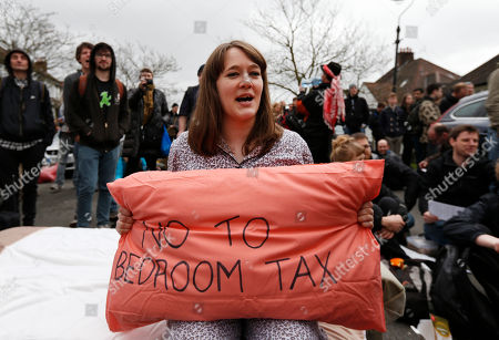 A protesters holds a pillow as she chants anti-cuts slogans during a protest outside the house of David Freud, Britain's Parliamentary Under Secretary of State for Welfare Reform, in north London, . Protesters from the Ukuncut Group organized actions across the UK as part of a campaign against the government's planned so-called bedroom tax and cuts to benefits
