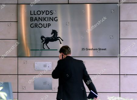 A man walks past the Lloyds TSB bank headquarters in central London, . Part nationalised Lloyds Banking Group has posted an annual loss of 1.34 billion pounds ($2 billlion) but reports an overall improvement in its financial outlook.The company said Friday its earnings had been hurt by the large amounts of money that had to be put aside to pay for mis-sold insurance products. Despite the losses the company says Group Chief Executive Antonio Horta-Osorio will receive a 1.48 million pound bonus (US$2.22 million