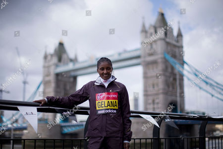 Elite women's marathon runner and reigning Olympic champion Ethiopia's Tiki Gelana poses for photographs during a media opportunity backdropped by Tower Bridge in London, . The London Marathon will go ahead on Sunday despite security fears in the wake of the bomb blasts in the Boston race that killed at least three runners and injured many more