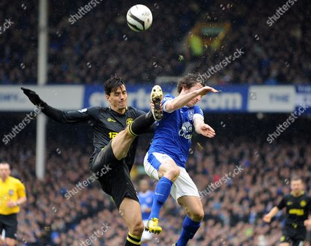 Everton's Leighton Baines right, and Wigan Athletic's Paul Scharner left, battle for the ball during their English FA Cup sixth round soccer match at Goodison Park in Liverpool, England