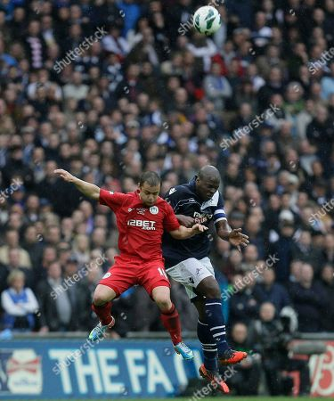 Millwall's Danny Shittu, right, jumps for the ball with Wigan Athletic's Shaun Maloney during their English FA Cup semifinal soccer match at Wembley stadium in London