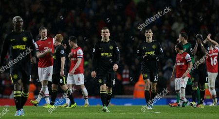 Wigan Athletic's James McArthur, centre left and teammate Paul Scharner walk towards their supporters after Wigan was relegated from the premier League following their 4-1 defeat by Arsenal in their English Premier League soccer match at Arsenal's Emirates stadium in London