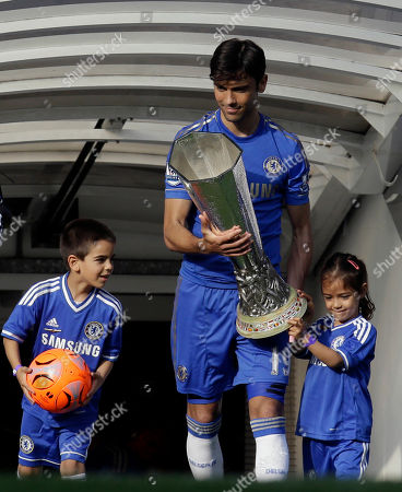 Chelsea's Paulo Ferreira walks with his unidentified children, onto the pitch carrying the Europa League cup to celebrate, following their English Premier League soccer match against Everton at the Stamford Bridge ground in London