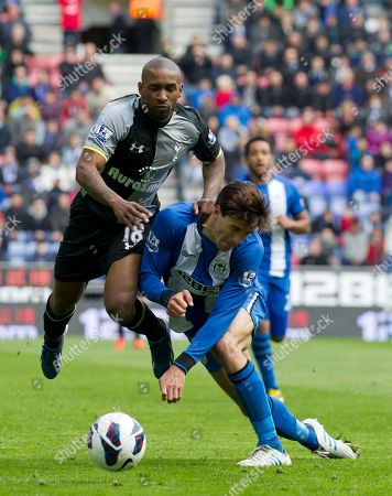 Tottenham's Jermain Defoe, left, fights for the ball against Wigan Athletic's Paul Scharner during their team's 2-2 draw in their English Premier League soccer match at The DW Stadium, Wigan, England