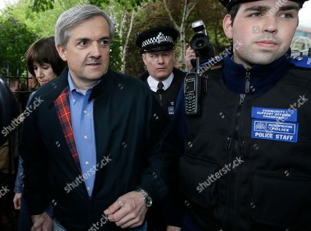 Former British politician and government minister Chris Huhne, left and his partner Carina Trimingham, arrive at their home surrounded by media, in London, Monday, May, 13, 2013 . Former British Cabinet minister Chris Huhne and his ex-wife Vicky Pryce have been freed from prison after each serving two months of their eight-month sentences. The pair had been convicted of charges stemming from a 2003 speeding ticket. Pryce had told authorities she was driving even though her then-husband was at the wheel