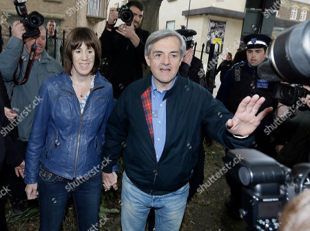 Stock Picture of Former British politician and government minister Chris Huhne centre, and his partner Carina Trimingham arrive at his home in London, Monday, May, 13, 2013 surrounded by media having served eight weeks of his sentence for perverting the course of justice over a speeding ticket. Huhne and his ex-wife Vicky Pryce were convicted after she took speeding points for him, they both served two months of an eight-month sentence