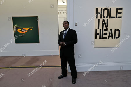 An auction house security employee stands guard, backdropped by works by artists Ed Ruscha, left, and Christopher Wool, right, at an exhibition in central London, . The pieces will be offered in auction at Sotheby's auction house Impressionist, Modern & Contemporary Art sales in New York, on May, 2013
