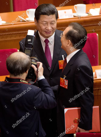 Xi Jinping, Wen Jiabao A photographer takes pictures of newly-installed President Xi Jinping, center, shaking hands with former Premier Wen Jiabao after the closing ceremony of the National People's Congress at the Great Hall of the People in Beijing . China's new leaders pledged to run a cleaner, more efficient government and slash spending on official perks Sunday as the ceremonial legislature wrapped up a pivotal session to install a new leadership in a once-a-decade transfer of power
