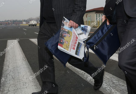 Delegates holding a newspaper with newly named Chinese Premier Li Kiqiang with former Premier Wen Jiabao, arrives at the Great Hall of the People in Beijing, China, . China's new leaders turned Saturday to veteran technocrats with greater international experience to staff a Cabinet charged with overhauling a slowing economy and pursuing a higher global profile for the country without triggering opposition