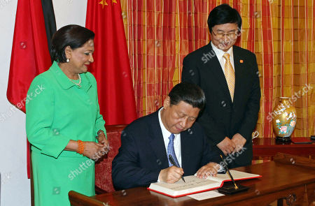 Xi Jinping, Kamla Persad-Bissessar Chinese President Xi Jinping, center, signs the guest book watched by Trinidad and Tobago's Prime Minister Kamla Persad-Bissessar, left, at the Diplomatic Center in St. Ann's, Trinidad. Xi meets his American counterpart Barack Obama on Friday, June 7 and Saturday, June 8, following stops in the Caribbean and Latin America as the leader of a more confident China following a decade of explosive economic and trade growth. From Trinidad to Mexico City, Xi presented Beijing as an important partner for developing countries and a source of markets and finance, handing out nearly $4 billion in loans and promising to boost imports