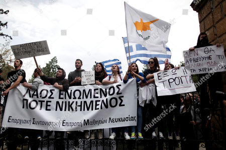 Cypriot students shout slogans as they stand at the entrance of the presidential palace in capital Nicosia, on . The banner on the left reads in Greek ''people united never divided''. Banks across Cyprus remain firmly padlocked Tuesday after financial authorities extended the country's bank closure, fearing worried depositors will rush to drain their accounts. The shut-down is hammering businesses, which have been without access to their funds for more than a week