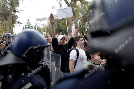 A riot police cordon secures the European Union house in Nicosia as Cypriot students shout slogans during a protest against the bailout package on . Banks across Cyprus remain firmly padlocked Tuesday after financial authorities extended the country's bank closure, fearing worried depositors will rush to drain their accounts. The shut-down is hammering businesses, which have been without access to their funds for more than a week