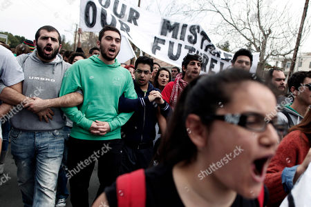 Cypriot students shout slogans during a protest against the bailout package in capital Nicosia, on . Banks across Cyprus remain firmly padlocked Tuesday after financial authorities extended the country's bank closure, fearing worried depositors will rush to drain their accounts. The shut-down is hammering businesses, which have been without access to their funds for more than a week