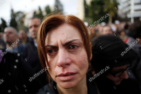 An employee of the Bank of Cyprus weeps during a protest at Cyprus central bank in Nicosia, Cyprus, . Cypriot businesses were under increasing strain to keep running on Tuesday after financial authorities stretched the country's bank closure into a second week amid fears that depositors will rush to drain their accounts