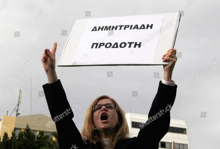 "An employee of the Bank of Cyprus holds a banner that read in Greek ""Demitriades Traitor"" and shouts slogans during a protest at Cyprus central bank in Nicosia, Cyprus, . Cypriot businesses were under increasing strain to keep running on Tuesday after financial authorities stretched the country's bank closure into a second week amid fears that depositors will rush to drain their accounts. Demitriades is a chief of Cyprus Central bank"