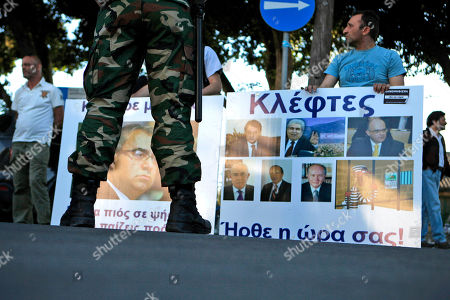 A riot police stands in front of protestors, with a banner display the image of the head of Cyprus central bank Panicos Dimitriades, and right, a banner displaying the image the president Nicos Anastasiades, former president Dimitris Christofias, and other members of parliament, during an anti-bailout protest outside of the Cyprus' parliament in capital Nicosia, . Cyprus' central bank says the Romanian operations of the island nation's largest lender Bank of Cyprus will resume April 26th after being suspended for more than three weeks amid plans to sell them off