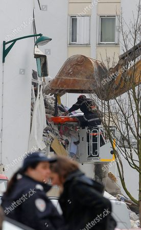 """French firemen remove the body of an unidentified victim from a building hit by an explosion that caused the collapse of its inside floors, in Reims, eastern France, . Five people was killed and ten others injured, according to firefighters, and Reims mayor Adeline Hazan said it awas """"a very powerful explosion"""" and the blast had the earmarks of a possible domestic gas explosion"""