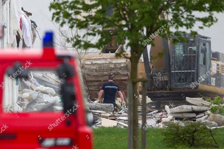 """French firemen attend the scene of a building hit by an explosion that caused the collapse of its inside floors, in Reims, eastern France, . Five people was killed and ten others injured, according to firefighters, and Reims mayor Adeline Hazan said it awas """"a very powerful explosion"""" and the blast had the earmarks of a possible domestic gas explosion"""