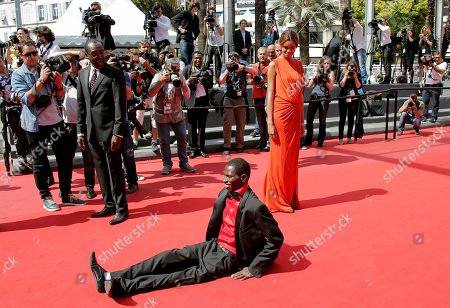 Mahamat-Saleh Haroun, Souleymane Deme,Anais Monory Actor Souleymane Deme, foreground, performs a dance as director Mahamat-Saleh Haroun, second left, and actress Anais Monory, right, watch him, as they arrive for the screening of Grigris at the 66th international film festival, in Cannes, southern France