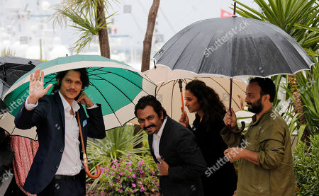 From left, actor Vijay Verma, actor Nawazuddin Siddiqui, actress Tannishtha Chatterjee and director Amit Kumar shelter under umbrellas during a photo call for the film Monsoon Shootout at the 66th international film festival, in Cannes, southern France