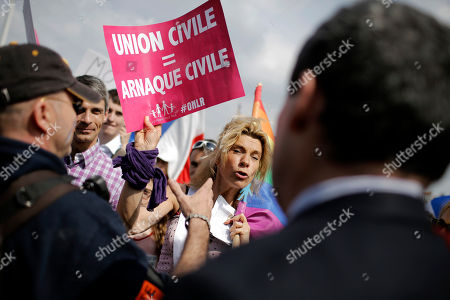 Frigide Barjot leader of the movement against gay marriage, centre, shows a placard as she confronts security staff members during a rally to protest against French President Francois Hollande's social reform on gay marriage and adoption, in Lyon, central France, . The placard says : civil union = civil scam