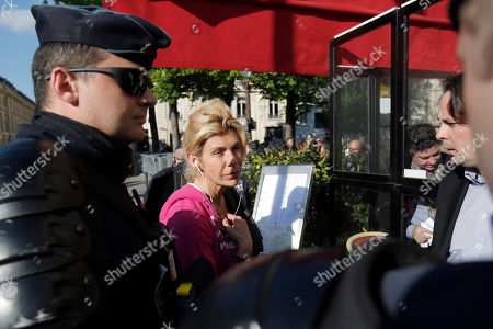 Virginie Tellenne, known as Frigide Barjot, leader of the movement against gay marriage faces policemen outside the National Assembly after French lawmakers legalized same-sex marriage, . Lawmakers legalized same-sex marriage after months of bruising debate and street protests that brought hundreds of thousands to Paris. Tuesday's 331-225 vote came in the Socialist majority National Assembly. France's justice minister, Christiane Taubira, said the first weddings could be as soon as June