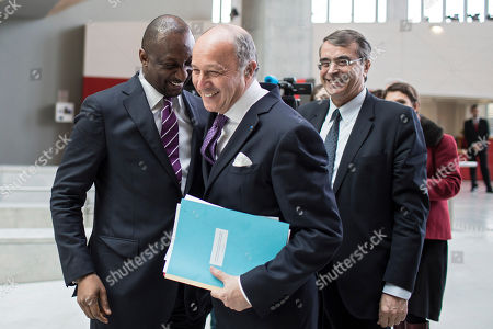 Stock Picture of French Foreign Minister Laurent Fabius, center, smiles with Mali's Foreign Minister Tieman Coulibaly, left, before a meeting in Lyon, central France