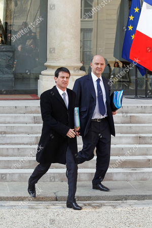 """French interior minister Manuel Vals, left, and economy minister Pierre Moscovici, right, leave the Elysee Palace following the weekly cabinet meeting in Paris, . French President Francois Hollande on Tuesday decried an """"unforgiveable moral error"""" by his former budget minister Jerome Cahuzac, who has jolted France's body politic by admitting on his blog to having lied about a once-secret foreign bank account"""