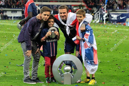 David Beckham Paris Saint-Germain's midfielder David Beckham from England, center, poses with the cup surrounded by his sons, Brooklyn, left, Cruz, second from left, and Romeo James, right, as he celebrates PSG's French League One title, at the Parc des Princes Stadium, in Paris, . The match was his final home game for Paris Saint-Germain before retirement